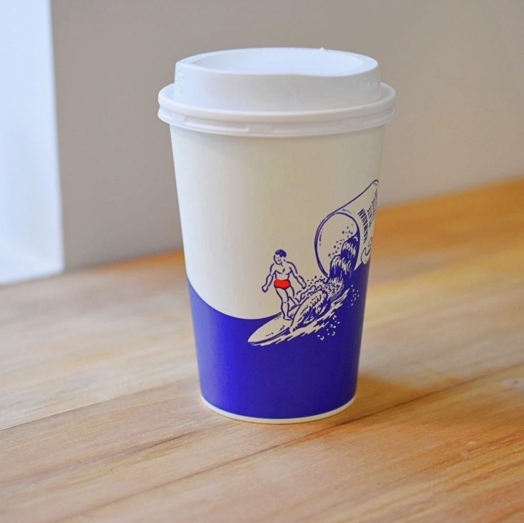 サーファーのイラストが描かれたオリジナルのコーヒーカップ