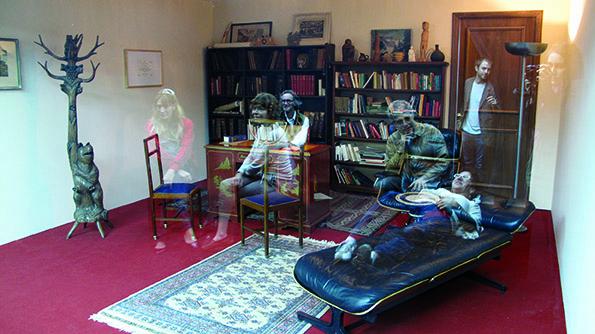 鏡にうっすら映った鑑賞者の姿がまるで亡霊のよう。《精神分析医の診察室》2005年 ソファ、本棚、机、椅子、カーペット、ガラス、照明のある同じサイズの2部屋 サイズ可変 展示風景:プロア財団、ブエノスアイレス、2013年撮影:Clara Cullen※参考図版