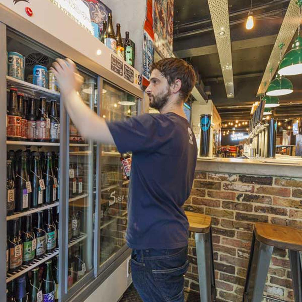 ボトル・缶ビールが並ぶ冷蔵庫は、カウンターのすぐ隣に。「BrewDog」をはじめ、英国の銘柄を中心にそろえる。