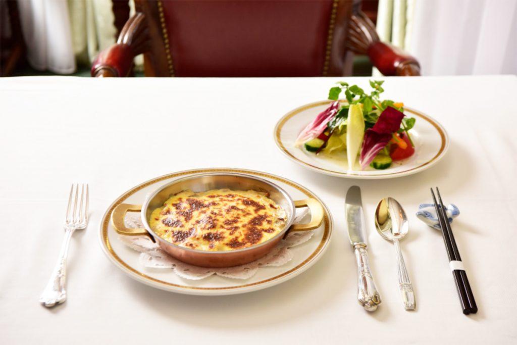 「芝海老のグラタン」2,900円(税込)(バターライスの上に、芝海老、タマネギ、マッシュルーム入りベシャメルソースをのせて。サラダ付き)は、50年以上続く定番メニュー。
