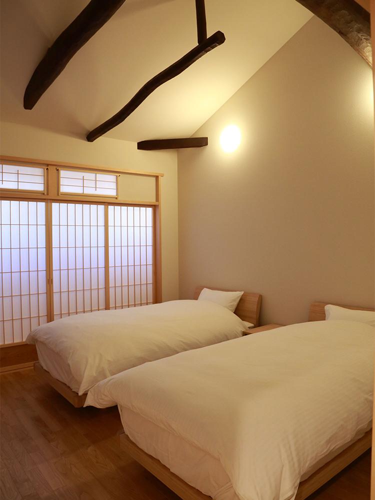 天井の梁に町家の趣を感じるシンプルなベッドルーム。宿泊の定員は最大6名。