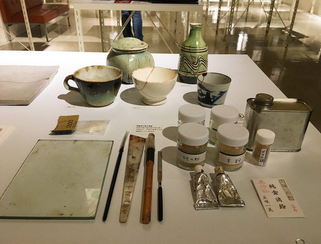 漆継ぎに使う漆や砥の粉や小麦粉などが並ぶ岩手県の展示スペース。桑原さんは「天然の材料だけで継いでるんですね」と興味津々。