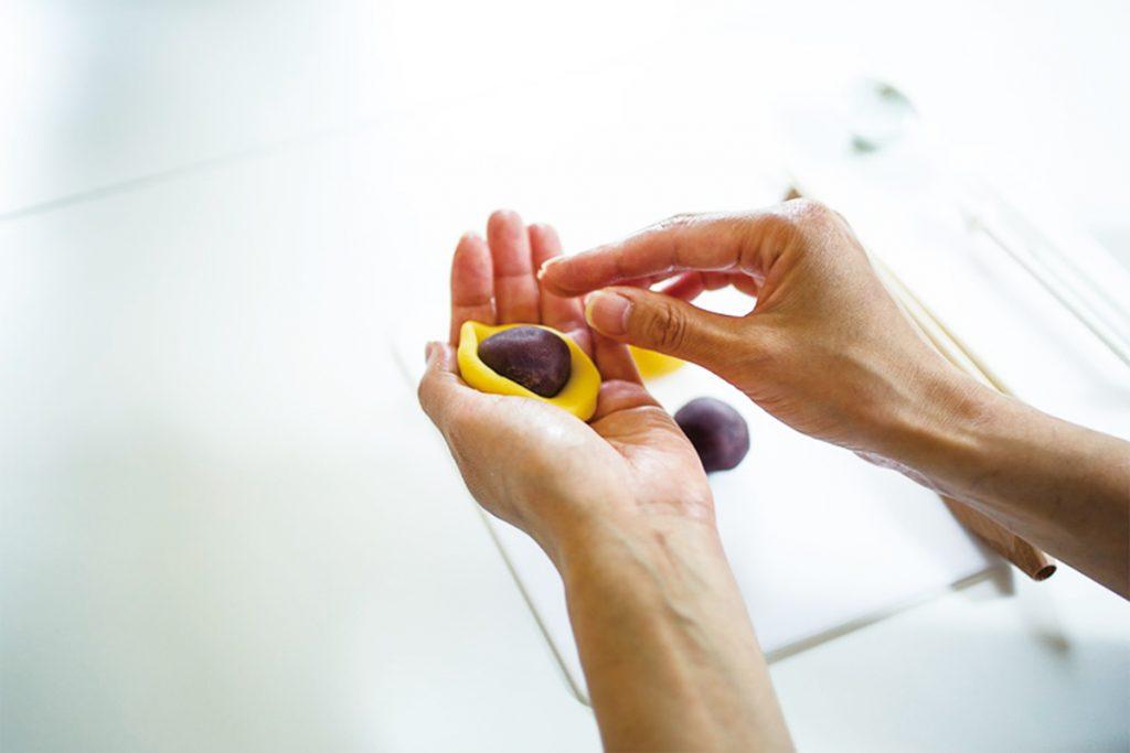 STEP1.白餡に求肥を加えた練り切り生地を手のひらで平たくのばし、その上にこし餡をのせて包み込んでいく。