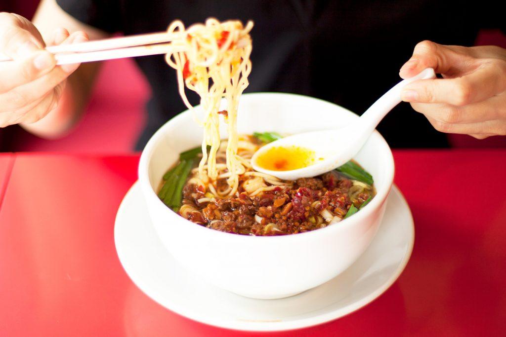 具材を混ぜて、コシのある中太麺とからめて食べる。写真はスタンダードな辛さの「台湾ラーメン」800円。辛さ2倍の「イタリアン」900円、辛さ控えめの「アメリカン」800円(各税込)もあり。餃子をはじめとした一品料理も充実。
