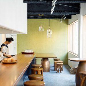 イエローグリーンの壁がカフェの爽やかさを演出している。一脚ずつデザインが異なるスツールはチークを一本彫りしたもので、こちらも〈ババグーリ〉のオリジナルアイテム。