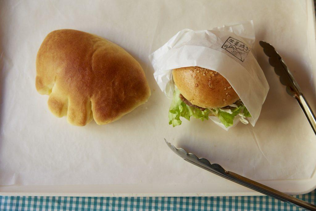 左が平日でも300個以上売れる「クリームパン」210円。右は「神楽坂バーガー 生姜焼き」310円。ほんのり甘いパンに、しょうゆ味の肉がよく合う。