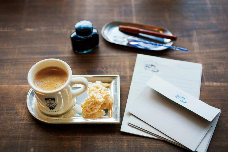深煎りコーヒー450円に、おやつを添えて。マグカップは人気のイラストレーター・柴田ケイコさんによるおじさんのイラスト付き。