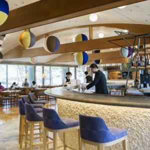 カラフルなオブジェが吊られたレストラン。窓の外には豊かな森林が広がる。