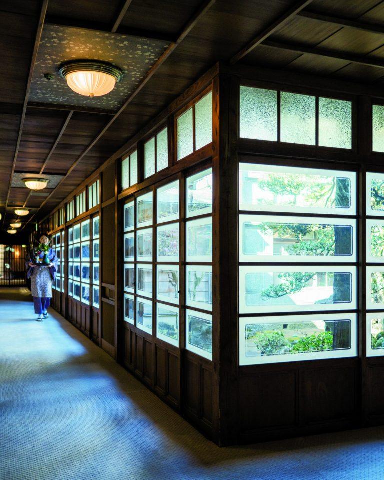 館内にある中庭のぐるりを囲む廊下。昭和初期の手仕事の、わずかに波打つガラス窓から覗く景色も、匠の意匠を今に伝える。