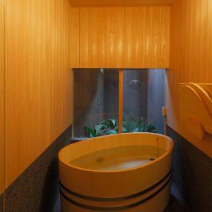 中村の建築の特徴である曲線美がヒノキの風呂にも。浴室の足元に切り取られた窓から自然光が差し込み気持ちがいい。