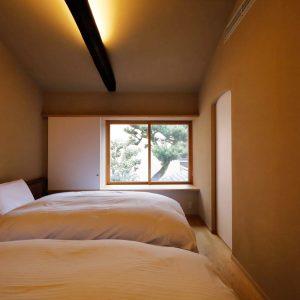 シングルベッドが2台並ぶ寝室。窓からは樹齢100年のイヌマキの古木が。
