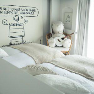 """© 2019 Peanuts Worldwide LLC ホテルのコンセプトでもある""""It's nice to have a home where your guests feel comfortable.(お客さんが居心地よく思ってくれるうちを持っているのは素敵だな)""""をテーマに掲げた61号室。白で統一されたモダンな空間で真っ白なスヌーピーが出迎えてくれる。窓の向こうには客室唯一となるテラスも。"""
