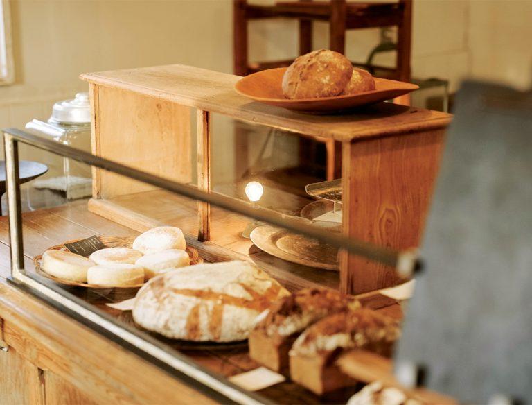 古い木のテーブルが陳列台。カンパーニュ(1g=1.1円)や黒糖くるみ 720円(各税込)など自家培養の種で焼いた美しいパンにうっとり。