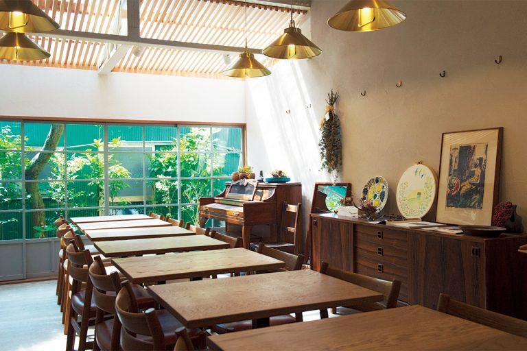 窓からの日射しが気持ちいい。大テーブルをイメージし並べたテーブルは、1960年代の椅子に合わせて特注。看板には山下さんが彫ったバゲットのロゴが。