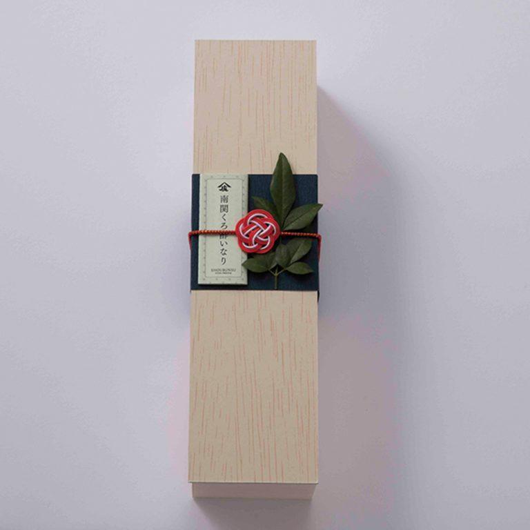 木箱の意匠も美しい、上質な手土産になる一品。いなり2個、くるみ味噌いなり3個、みょうがいなり3個入り1,800円(具材は季節により変わる)。