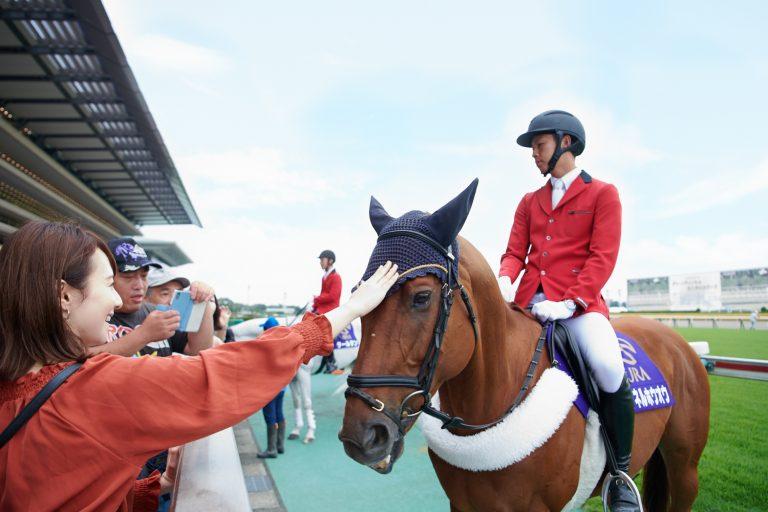 誘導馬のおでこをナデナデする小林さん。「毛がサラサラで目がキレイ!」と、馬との触れ合いに感激のご様子。