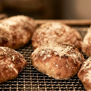 くるみクランベリー、ヨモギ大納言、カシューナッツ黒胡椒など色とりどりの個性的なパンが次々とオープンキッチン内で焼かれる。