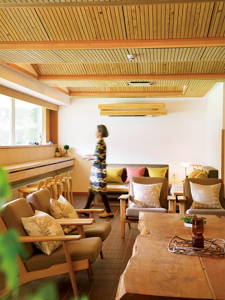 北欧デザインの家具やファブリックが、まるで自宅のリビングにいるかのように落ち着く〈ホテリ アアルト〉のラウンジ空間。窓の外には天然の庭園―深い森が広がる。ワンピース 36,000円(マリメッコ|ルック ブティック事業部 03-3794-9139)/サボ 24,000円(ダンスコ|シースター 03-6427-9440)