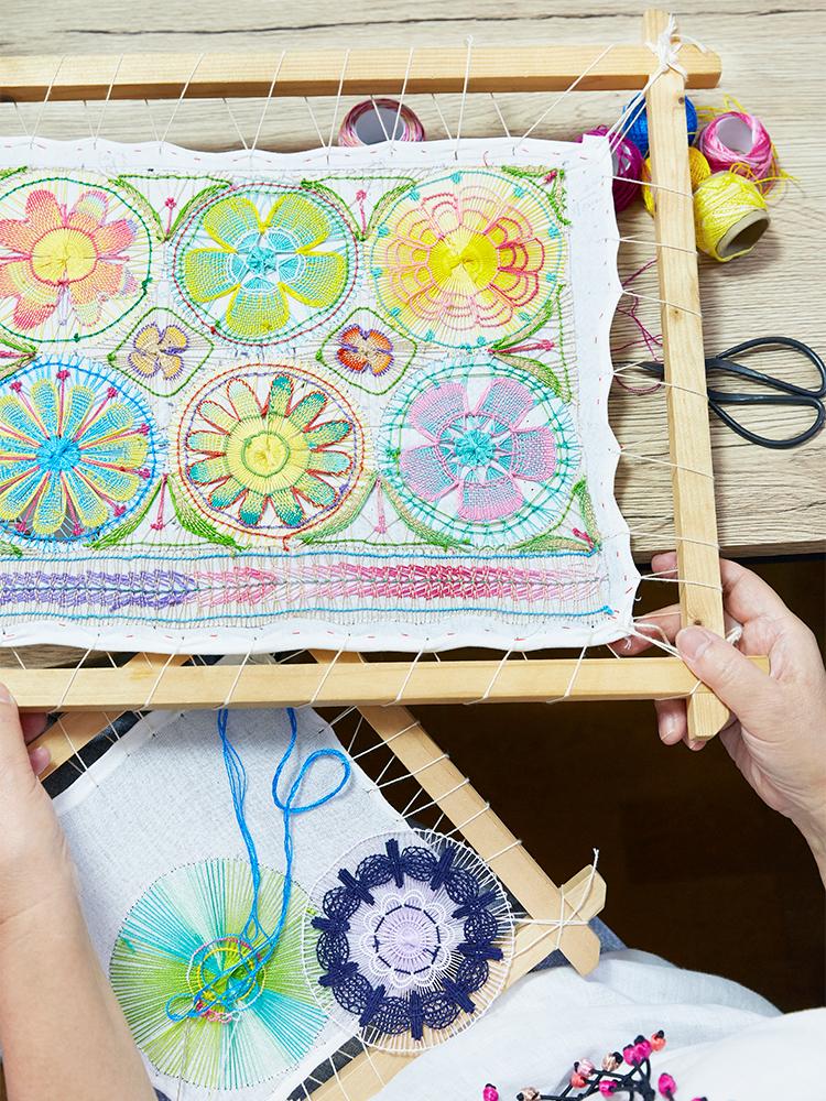 木枠にくくり付けた布地いっぱいにニャンドゥティを編んでいく。同じ図案でも、糸を変えると印象ががらりと変わるのがおもしろい。