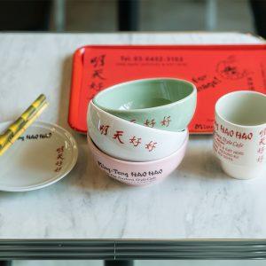 店舗やグッズのデザインは〈DEPT〉のディレクター兼デザイナー、eriさんによるもの。器は長崎の波佐見町で製作された波佐見焼。使い勝手もよいので自宅用に買い求める人も多い。ロゴもキッチュな世界観を表現している。ギフトにも。右から、明天大茶杯 3,500円、明天汁椀各3,000円、明天取分小皿 2,500円、唐竹吸込藁(ストロー・25本入り)600円。