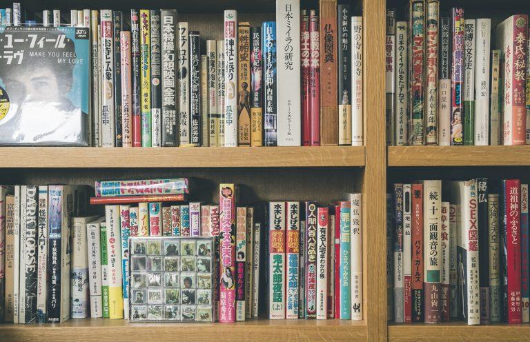 引越し業者のおばちゃんが入れたままの状態が保たれた本棚。秩序のない並び順が味わい深い。
