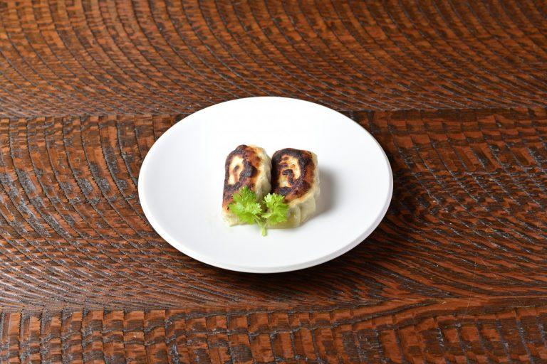 """餃子。具材は乳酸発酵させた白菜、舞茸、きくらげ。米をつぶしてきりたんぽ状にしたものを""""餡""""のつなぎに使っている。"""