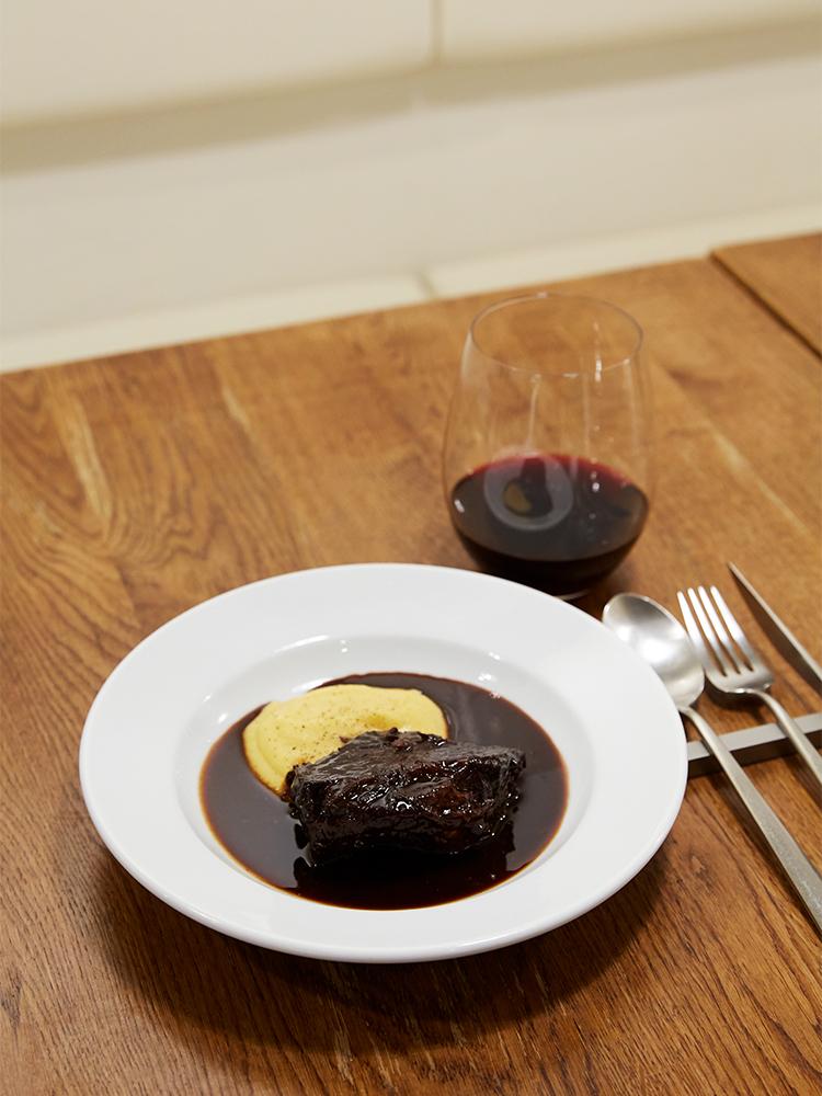 「ニュージーランド産牛ホホ肉の赤ワイン煮」2,800円、「高橋葡萄園 メルローの赤ワイン」950円(グラス)。料理は1人で来店した場合のみ、ハーフポーションで提供可能(価格も半額)。写真はハーフポーション。