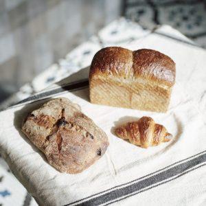 奥から時計回りに、「たねものパン」1,200円、「クロワッサン」270円、「サングリアロッソ」840円。惣菜パンや菓子パンではなく、生地のおいしさで真っ向勝負。