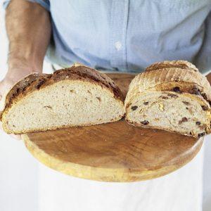 """お店の近くにある〈秋山農園〉で採れる小麦粉""""農林61号""""と、自家焙煎したルヴァンで作られ、ぎゅっと詰まった生地は香り豊か。「カンパーニュ」1,000円(税込)、「ドライフルーツ・ナッツ入りホール」1,600円(税込)"""