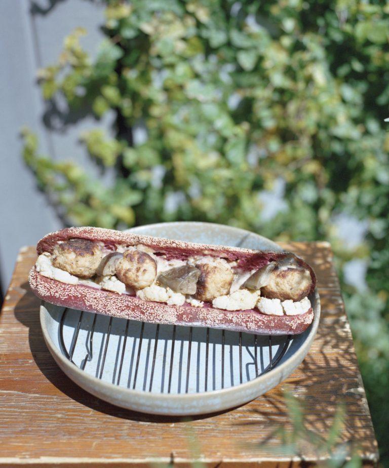 「鶏とカリフラワー」470円。ビーツ入りパンに、厳選したつくね、ローストしたカリフラワー、ナスをはさみ、自家製ゴマドレで味付け。パンも具材もすべてクミンでまとめあげる。