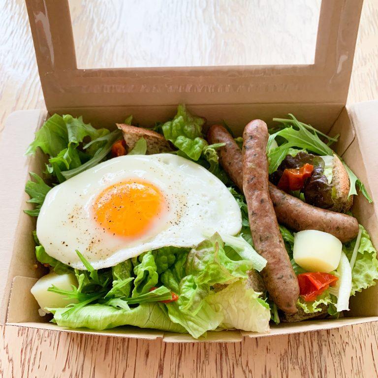 「サラダ風サンドイッチ-目玉焼きとソーセージ」1,120円。有機野菜のグリーンサラダの中にトーストした一口大の自家製パンを入れて、岐阜のハム工房ゴーバルさんの無添加の季節の野菜ソーセージ、平飼い卵の目玉焼きをのせて。