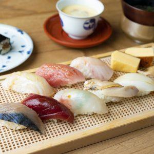 【ランチコース・4,000円】握り9貫+玉子焼き+巻物+茶碗蒸し+お椀下/右から、穴子、スミイカ、蛤、鰆、鮪、しめ鯖。上右から、玉子焼き、鯛の昆布締め、中トロ、平目。左上はかんぴょう巻き。これに茶碗蒸しとお椀がつく。その日の魚の状態に合わせて、赤酢も白酢も自身でブレンドする。「使っている魚介もとても上質で仕事も細やかです」