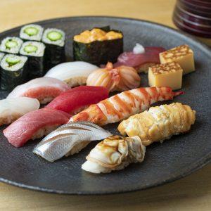 【ランチコース・5,000円】握り12貫+玉子焼き+巻物+お椀 左下から、ハマグリ、穴子、小肌、車海老、玉子焼き、トロ、鮪、赤貝、鰹、平目、金目鯛の昆布締め、イカ、ウニ、かっぱ巻き。初鰹にはその都度、新玉ねぎをすりおろしてのせる。煮蛤は希少な東京湾産天然物の真蛤。ふっくら。「プリンのように舌触りがなめらかな玉子焼きも必食!」