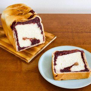 〈トミーズ〉の大人気商品「あん食」700円(税込)。北海道産の小豆を使った独自の粒あんを、生クリーム入りのふんわりした味わいのパン生地に混ぜ合わせた新感覚の食パンです。カットしてみると、耳の近くまでしっかりと粒あんが練り込まれているのがわかります。到着後はそのまま生で食べるのがおすすめということで、贅沢に少し厚めに切っていただきます。ふわふわ、もっちりとした生地に、あんこの甘みが絶妙にマッチ。これ一枚でお腹いっぱいになるほどのボリュームです。