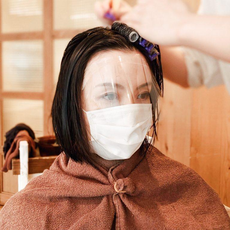 ビフォーは顎のラインのミディアム。ふんわりしたボリュームが欲しくて伸ばしっぱなしにしていた分、まとまりにくくなってきたのが悩み。ついでペタンコになりやすい根元をふんわり可愛く立ち上げたい!髪の生え際に細いロットを巻いてパーマ液を塗るので顔に液が垂れてしまわないようフェイスシールドで万全のそなえを。