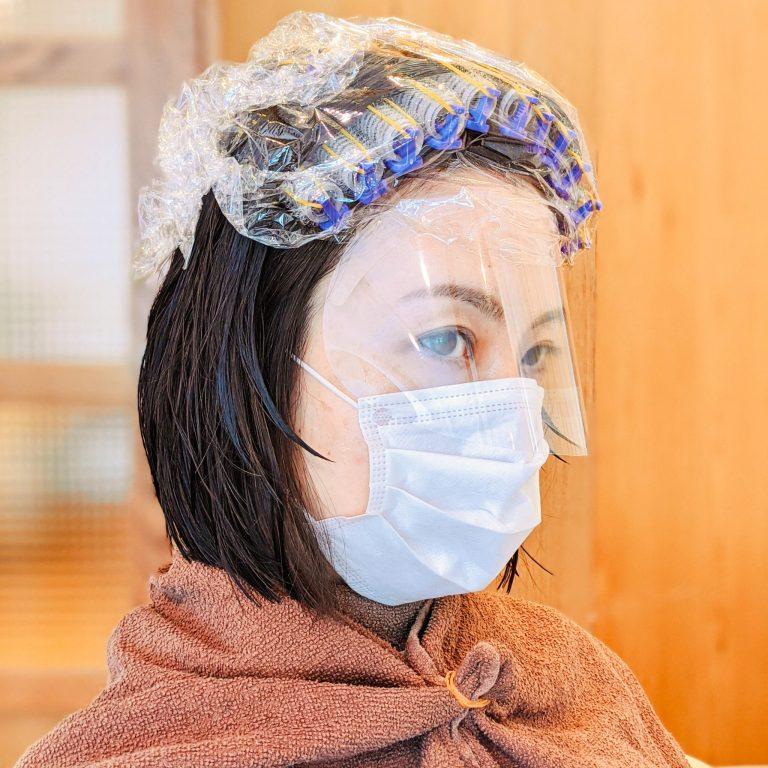 コロナ対策でマスクの着用もばっちり。仕上がりを計算しつつ、丁寧にロットを巻き上げます。根元の毛の生えグセや立ち上がり方を考慮しなければいけないから、簡単そうに見えて熟練のテクニックが必要。  パーマと言っても、部分的なニュアンスパーマなので工程も拍子抜けするほどスムーズ。