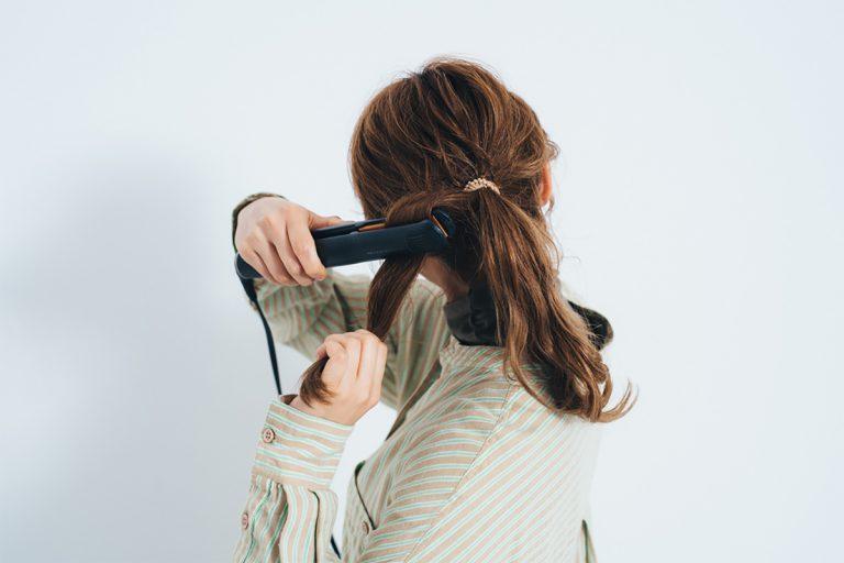 1.毛束をざっくりと太めに取り、結び目下を床と平行にアイロンで挟む。まずは内側へ半カール。