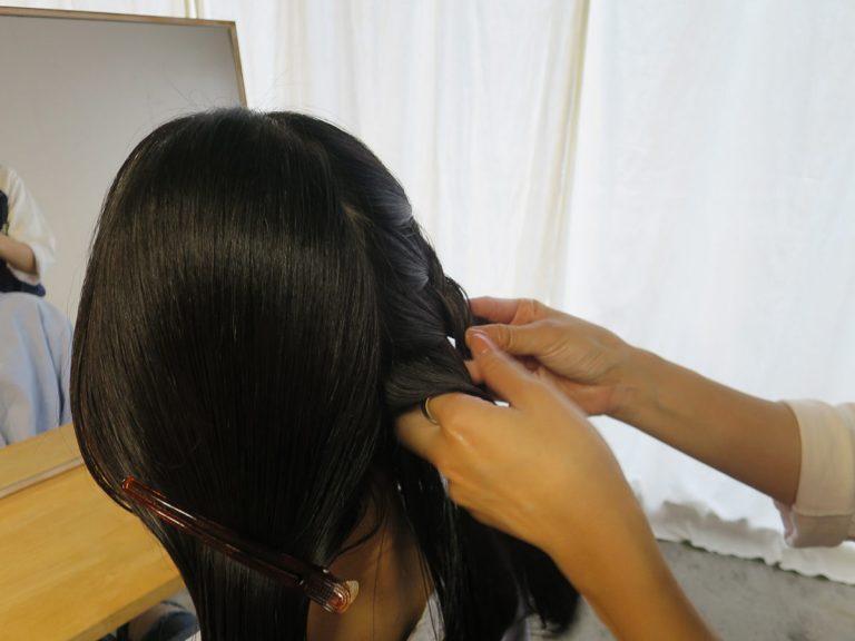 """手にワックスを広げて編み込み開始。頭の""""はち""""部分で髪を取り、3つに分けた毛束に少しずつ残りの髪を足しながら編んでいく。このとき、編んでいない側の髪(写真では左半分)はクリップで留めておくとスムーズ。"""