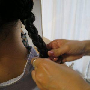 三つ編み部分までゆるみのないように。 編み込みは頭の形に沿って、ゆるみのないよう進めていく。襟足まで来て三つ編みに切り替えたら、束の量を不ぞろいにして表情をつけるのがポイント。