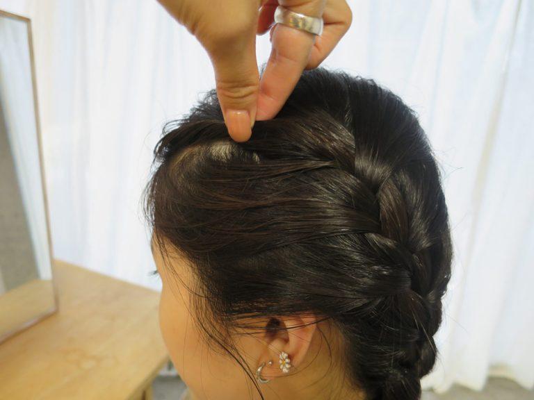 左右対称にするコツは、最初に取る髪の量を同じにすること。顔まわりの産毛や残った前髪は、ねじってピンで留め、アクセントに。 「ただの編み込みだけだと、印象が弱め。前髪をねじってピンで留めるだけで、こなれて見えます」(yukiさん)。
