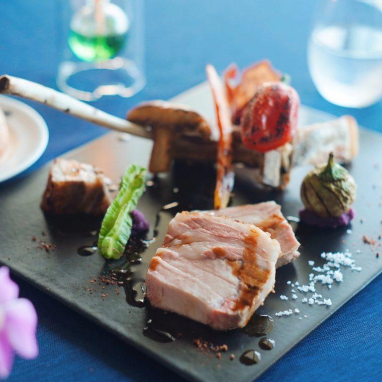 ディナーは、基本的には沖縄食材を使って調理した沖縄の土地に合わせた沖縄フレンチ。料理は連泊をする方がいらっしゃるため、続けては同じものを出さない工夫をしているそう。「今帰仁アグーのロースト」。部位は仕入れる時の1番いい状態のものを出しているそうです。周りには島胡椒や塩も。魚はその日に釣れたものを調理しているそう。