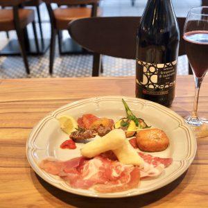 「Carpi e Sorbara ランブルスコ グラスパロッサ ディ カステルヴェトロ DOP」グラス450円と、試食用に特別に提供された前菜盛り合わせ。