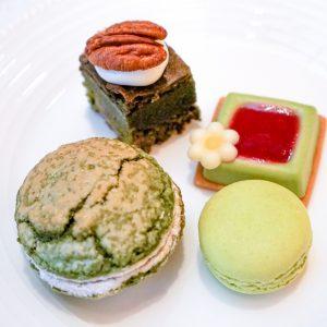 左前:抹茶ダックワーズ、左奥:抹茶チョコレートブラウニー、右奥:抹茶とラズベリーのレアチーズケーキ、右前:抹茶マカロン。