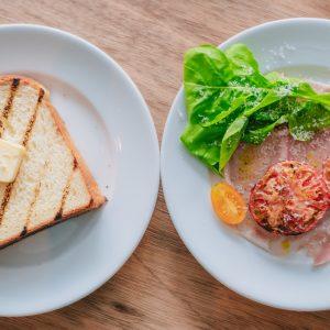 「炭焼きバタートースト&トマトのグリルとハム、ルッコラ、パルミジャーノのプレート」 炭焼きグリルの焼き目が食欲をそそるトーストは、池尻大橋の〈TOLO PAN TOKYO〉から仕入れたパン。厚切りで食べごたえも抜群。香ばしい炭の香りと共に幸せが広がります。 産地から届けられる自慢のお野菜は、炭焼きという原始的な調理法が抜群に合う。贅沢にトーストの上にのせて食べてヨーロッパ風の朝食に。