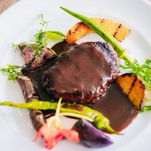 「淡路島産ビーフハンバーグの炭焼きステーキ デミグラスソース」 見た目にも美味しいランチのハンバーグプレートは、添えられた野菜たちが主役級の美味しさ。野菜の食感を残した絶妙な焼き加減に、炭焼きでこそ再現できる野菜の甘みに驚くこと間違いなし。