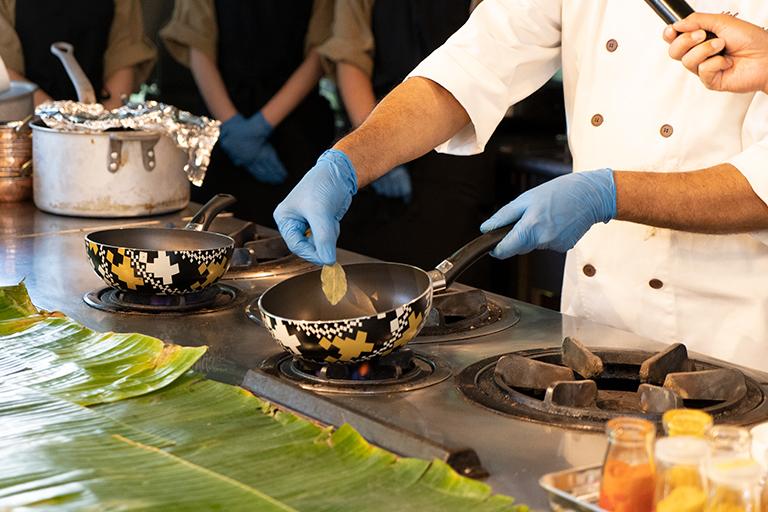 フライパンの中で温めた油にベイリーフやシナモン、カルダモン、グローブと炒ったホールスパイスを加えて香りを出します。