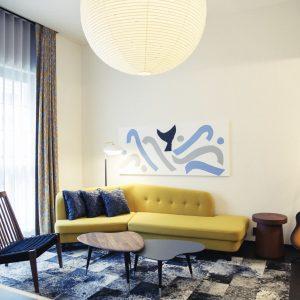 アートがちりばめられた空間。/正面には柚木沙弥郎の作品。カーテンは〈ミナ ペルホネン〉の別注。客室によってはレコードプレーヤーやギターがあるのも〈エースホテル〉らしい特徴。