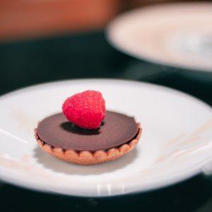 「タルトレット・ショコラ/フランボワーズ」 個人的なおすすめが、真っ赤なフランボワーズが目を惹くタルトレット。薄くパリパリとしたショコラの下には、ル・ショコラ・アラン・デュカスオリジナルブレンドの75%のショコラクリーム、フランボワーズのマーマレード、そして軽やかな食感のタルト。「パリットロッサクッ」が一口で味わえる至福のクリエーションです。フランボワーズの甘酸っぱさは言わずもがな、ショコラにぴったり。
