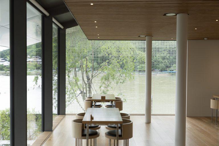 緑と水を感じながらくつろげるカフェスペース。深いひさしがガラスの反射を抑え、外の景色を美しく映し出す。家具と床には無垢材を使用。