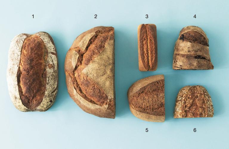 おまかせ便(5,000円セット、税込)。1.白いパン、2.茶色いパン、3.パンブリオッシュ、4.くるみとレーズンのパン、5.黒いパン、6.ひまわりのパン。葡萄種とホップ種を使用した白いパンは食パンのよう。パンブリオッシュは地元の〈あすなろファーミング〉のバターを使用する贅沢さ。茶色いパンは自家製粉20%のカンパーニュ。黒いパンは自家製粉した全粒粉100%。